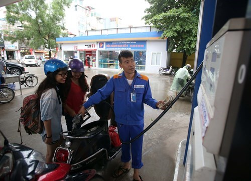 Two women have their motorbike refilled at a gas station in Hanoi. Photo: Ngoc Thang