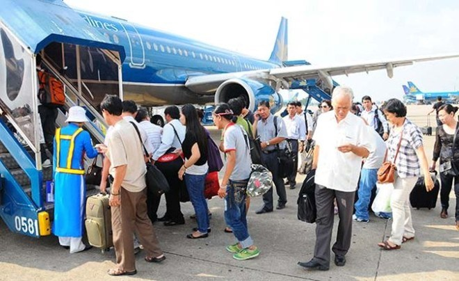Passengers step on a plane at Tan Son Nhat Airport. Several who have failed to pay the fines for recent flying violations now face a flight ban. Photo credit: Zing
