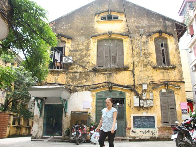 A woman walks past a 95-year-old colonial house in downtown Hanoi, which is home to 17 families of people who are serving or used to serve in the military. The house and many of its kind are in bad conditions. Photo: Minh Hoang