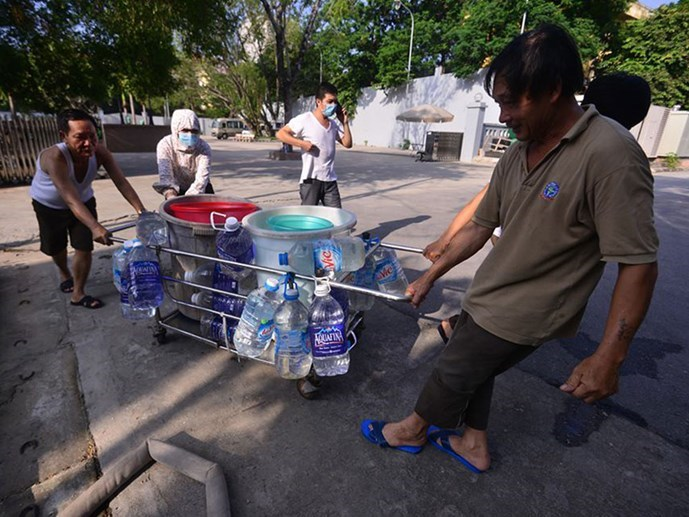 People pull water collected from the back-up tank of a hospital in Hanoi to store in their rooms as all tap water has run out. Photo: Dung Minh