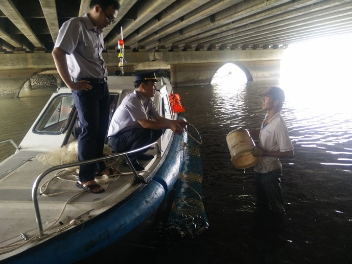 Ho Chi Minh City officials order a man to release nearly 20 kilograms of fish he caught on Friday morning back into the Nhieu Loc-Thi Nghe Canal. Photo: Cong Nguyen