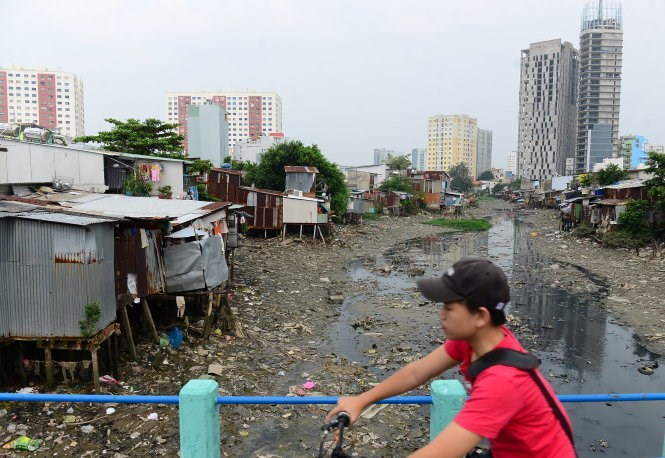A boy rides past the Cau Bong Canal in Binh Thanh District on October 5. Houses have been built all over the canal. Photo credit: Tuoi Tre/Quang Dinh