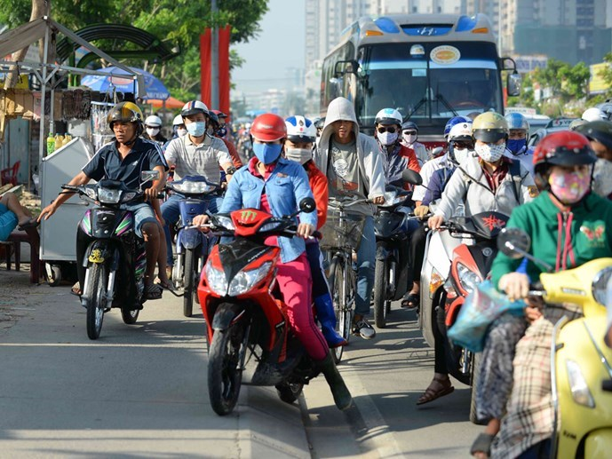 Most bike riders in Ho Chi Minh City wear face masks to protect themselves from dust. Photo: Diep Duc Minh