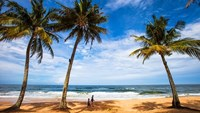 Tourists walk on a beach in Phu Quoc Island in southern Vietnam. Photo credit: Shutterstock