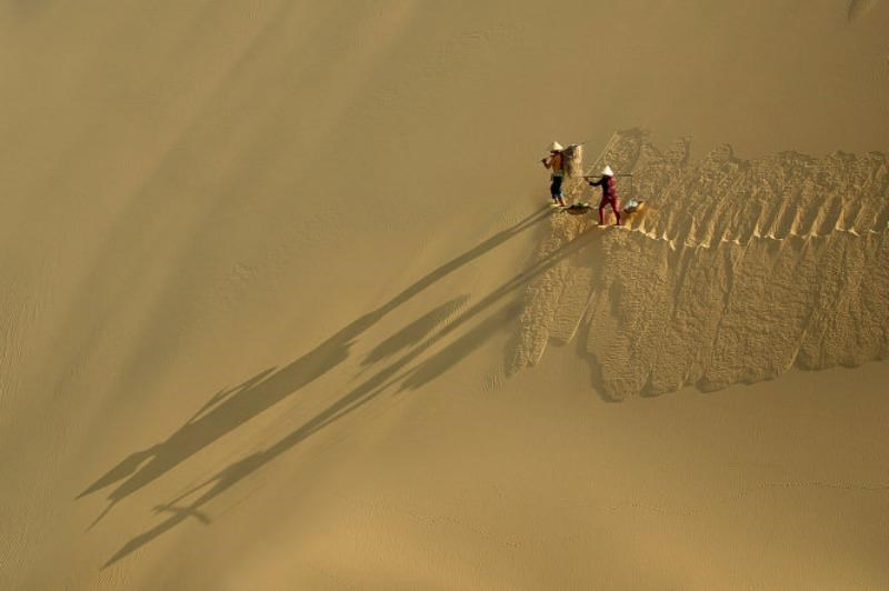A photo by Le Minh Quoc shows two vendors walking by a sand dune to bring their merchandise to the market. It is prized as the best for the East Asia-Pacific region at the World Bank photo contest.