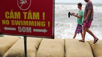 "Foreigners walk past a ""No swimming"" board along the coast of Hoi An. Erosion has badly destroyed the town for years. Photo: Minh Hoang/Zing"