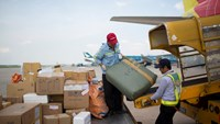 Men load baggage from a plane at Noi Bai Airport in Hanoi. Photo: Brent Lewin/Bloomberg