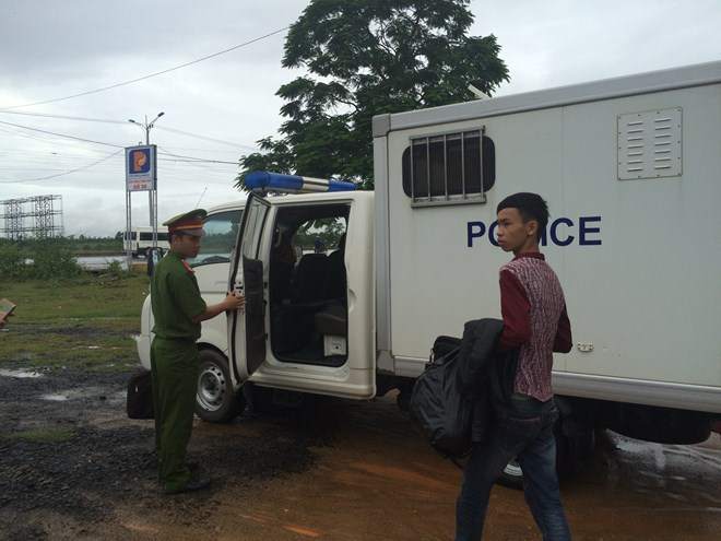 Le Van Tu walks to a police vehicle after his Facebook scammed was busted last week. Photo: Thanh Tuyen