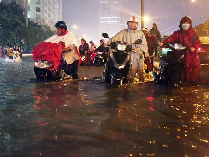 People struggle to push their bikes through a flooded street in Ho Chi Minh City. Photo: Dao Ngoc Thach