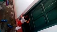 A scene taken from a video shows a 2-year-old boy locked outside a classroom in Lang Son Province as his teachers punished him for not taking a nap.