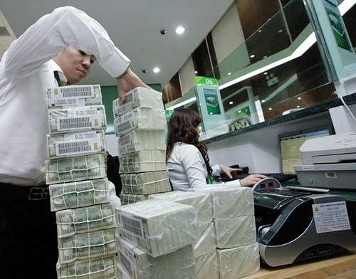 An employee at a Vietcombank office in Hanoi arranges pack of dollar notes. Photo: Ngoc Thang