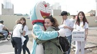 "Nguyen Bao Ngoc in a Doraemon costume offers a hug to a foreigner in Hanoi. Photo courtesy of the ""Hug Me"" campaign"