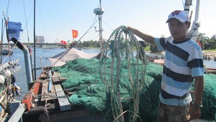 Dao Ngoc Duc, a fisherman from Da Nang, raises his fishing nets which he said had been damaged by Chinese boats in the Gulf of Tonkin on November 14. Photo credit: Nam Cuong/Tien Phong