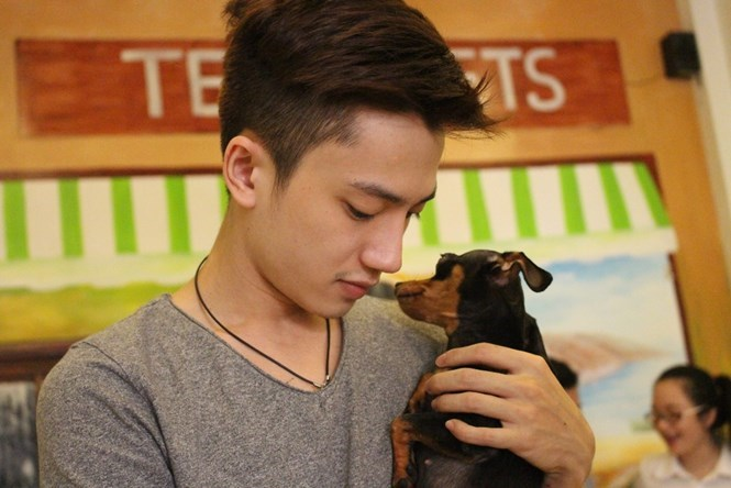 Le Hoang Duy with one of the two dogs surviving the poisoning that killed 13 others at his pet cafe on November 13, 2015. Photo: Vu Phuong