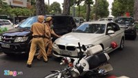 Police try to stop the BMW on Nam Ky Khoi Nghia Street after the driver hit their motorbike to fall. Photo credit: Zing