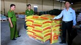 Police with sacks of tainted animal feed found at a producer in the northern province of Hai Duong on November 16. Photo: Xuan Long