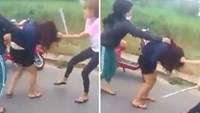 A still from a video posted on YouTube shows a girl trying to hit another with a cane, with the help of her friend in Da Nang