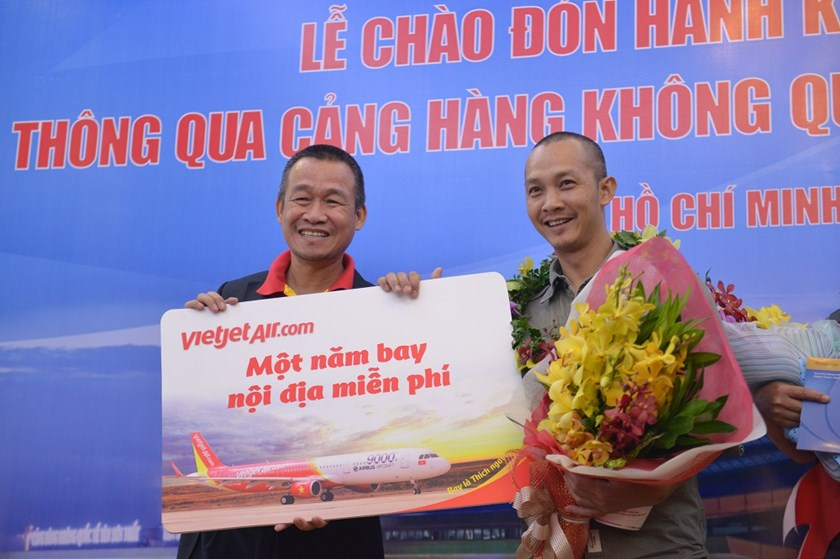 Nguyen Quang Son (R) from Hanoi will receive one year flying with Vietjet for free for being its lucky 24,999,999th passenger.