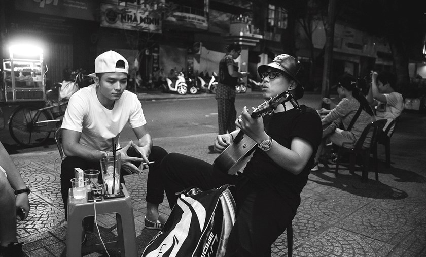 Young men play music by the sidewalk stool at a coffee shop that serves through the night in District 1. Photos: Thien An