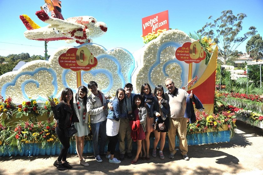 Tourists pose with Vietjet's float at a carnival held by the airline at Da Lat's ongoing flower festival