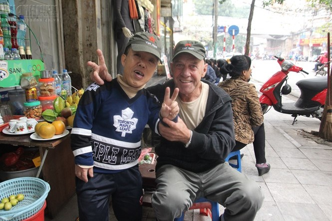 Dinh Van Phu (L) and a foreign friend at his coffee shop in Hanoi. Photo: Le Nam