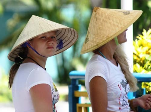 Russian tourists wear Vietnamese traditional hats in Nha Trang. Photo: Nguyen Chung