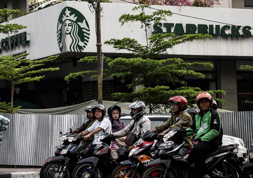 Indonesians wait at an intersection outside the damaged Starbucks building in Jakarta on January 15, a day after a series of explosions hit the Indonesian capital. Photo: Manan Vatsyayana/AFP