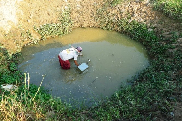 A farmer in the Mekong Delta province of Tra Vinh takes water from a shallow pond. The province is among the country's hardest hit areas in this year's dry season. Photo credit: Minh Anh/Zing