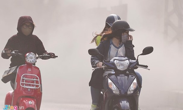 Bike riders ride past a dusty road in Hanoi. Photo: Le Hieu/Zing