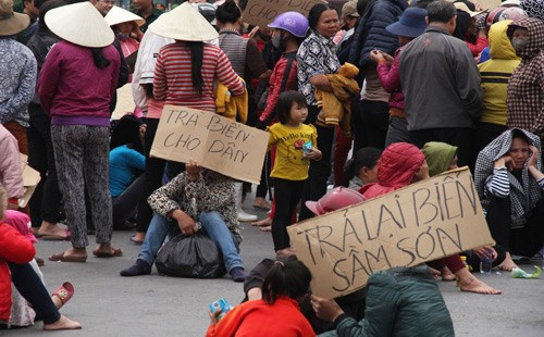 People in Thanh Hoa Province hold cardboards that demand Sam Son beach be returned to the public on March 3. Photo credit: Le Hoang/VnExpress