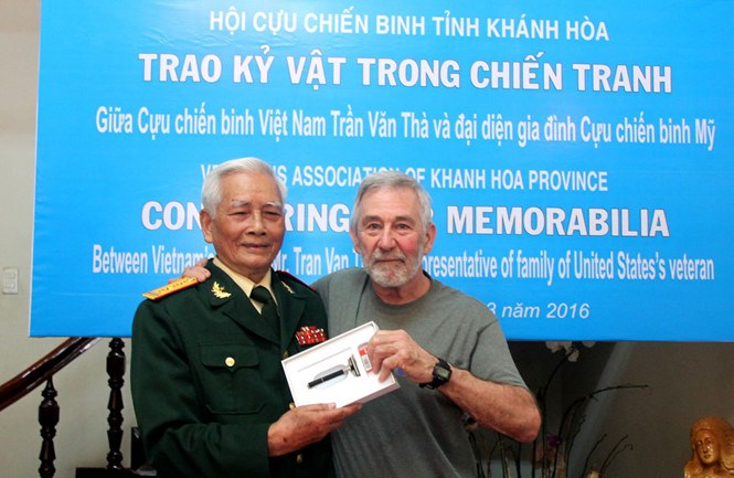 Tran Van Tha (L) returns a razor of an American killed during the Vietnam War to his former comrade. Photo: Tran Cong Thi