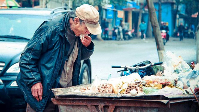 An old man eats noodles he picks up from a garbage cart in Hanoi. Photographer: Nguyen Son Tung
