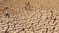 Children walk on a dry, cracked field in the Mekong Delta. Photo: Cong Han