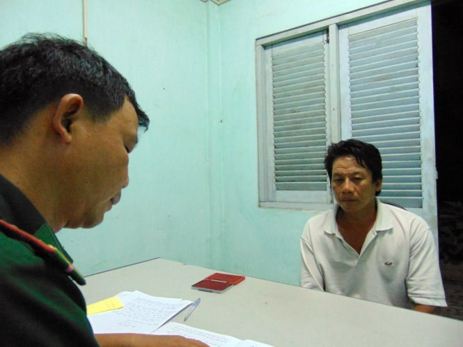 A border guard officer in Vung Tau questions a man for alegedly stealing from a Portuguese ship May 11. Photo credit: Dong Ha/Tuoi Tre