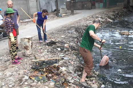 Two foreign men and local women pick up trash from a Hanoi canal in a photo dated May 15, 2016. Photo credit: Keep Hanoi Clean