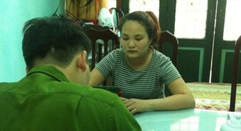 Le Thi Thanh Dam, 22, is questioned by a police officer for allegedly selling women into a sex ring. Photo: Hoang Long