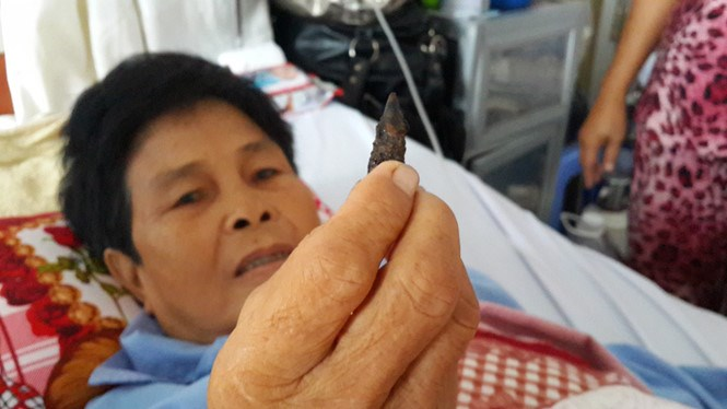 Nguyen Thi Cat holds the rusty bullet that has been removed from her body. Cat's husband said the bullet hit her chest one day in 1971 during the war when she was cleaning the backyard at her home in Kien Giang Province. Photo: Dinh Tuyen/Thanh Nien