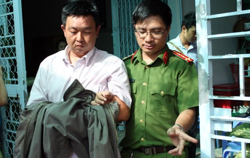 Vo Hoang Anh (L), a senior traffic inspector, is arrested at home in Can Tho City for allegedly soliciting bribes. Photo provided by police