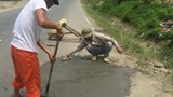 Two men fix a pothole on a highway in Lao Cai Province in a photo published on Facebook.
