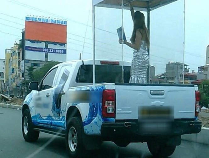 A vehicle carries a woman in a box around Hanoi on August 11 to advertise a new phone. Photo credit: Tuoi Tre
