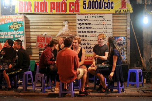 Foreigners at a sidewalk beer shop in Hanoi's Old Quarter