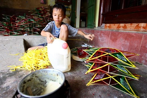 A boy places the yellow strips on the lanterns. Locals say making lanterns are a turnover business. The more you sell, the better. Hence a lot of hard work is involved and families deploy as many people as they can, with children helping out with the smaller, easier tasks.