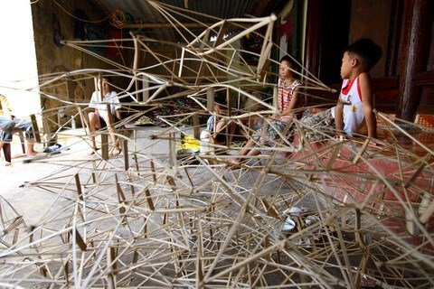 Boys sit by a pile of bamboo frames that will be used to make the star lanterns.