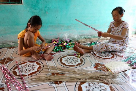 A girl helps her mother decorate a thin stick that will eventually circle the stars.
