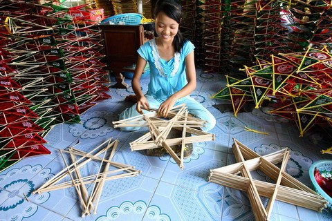 A girl arranges the star bamboo frames. Each lantern has two star frames stuck together. Small sticks are put between the frames to make the lantern swell up, and then cellophane paper is glued on.