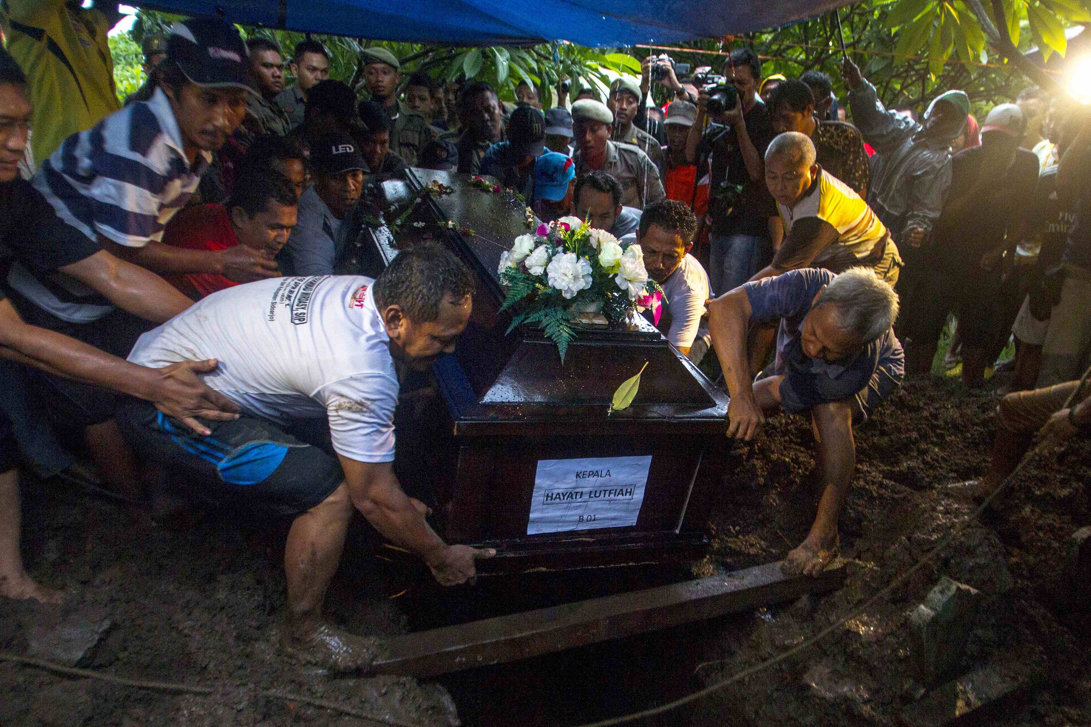 Weather stalls search for AirAsia black boxes; first victim buried