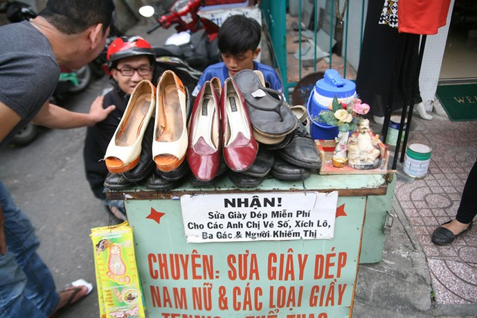 Young shoe repairman offers free service to the poor in Saigon alley